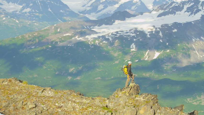 Aerial top of the world view of male mountain climber in summer enjoying success high Peaks Troublesome Glacier Chugach Mountains, Alaska, USA shot on RED EPIC, 4K, UHD, Ultra HD resolution