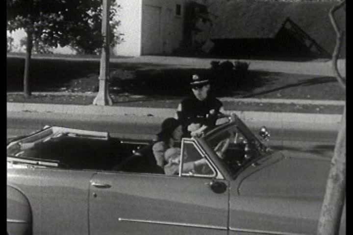 A police officer gives a woman a ticket for committing a traffic violation during the 1940s   Shutterstock HD Video #5318990