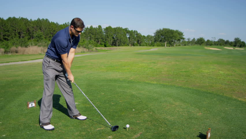 Professional golfer taking swing hitting golf ball off tee on golf course fairway slow motion shot on RED EPIC, 4K, UHD, Ultra HD resolution