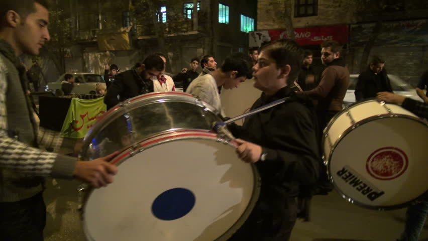 TEHRAN, IRAN - 11 NOVEMBER 2013: Young men are playing drums as they prepare for Ashura, part of Muharram, the main religious event for Shia muslims, in Tehran