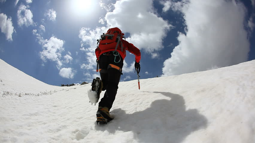 Mountaineer walking uphill along a snowy slope. Rear view. Western Alps, Europe. HD1080P #5364734
