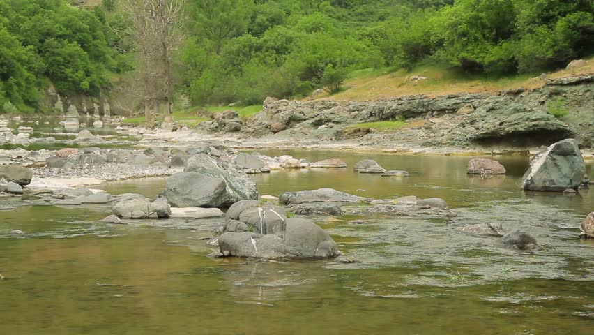 Small beautiful river flows between rocks and trees. A perfect spot for fishing. Rhodope Mountains, Bulgaria.