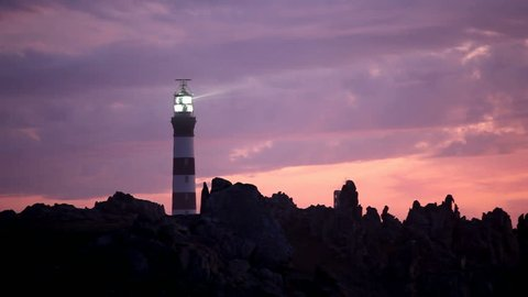 powerful lighted lighthouse at dusk, ouessant island, brittany, france