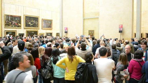 """PARIS - JAN 02: Visitors take photos of Leonardo DaVinci's """"Mona Lisa"""" at the Louvre Museum on January 02, 2014 in Paris, France. The painting is one of the world's most famous works of art."""