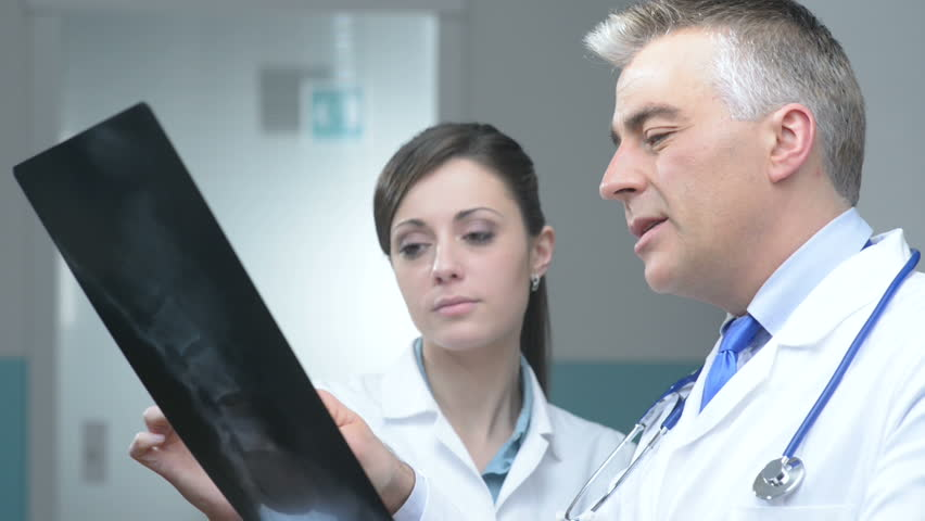 Doctor and assistant looking at patient's x-ray and pointing | Shutterstock HD Video #5434910