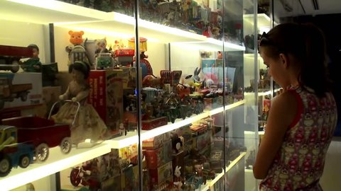 SINGAPORE - JULY 05: Girl at the showcase with rare vintage toys. July 05, 2010 in SMINT Museum of Toys, Singapore.