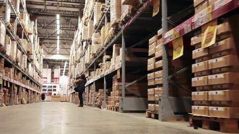 Buyer standing at big wholesale shop warehouse and choosing goods
