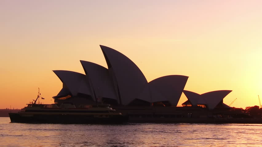 SYDNEY -December 2008: Sydney, Australia. Sydney Opera House time lapse at dawn. A huge cruise ship enters the harbour before the sun rises behind the Opera House. Ferries move across the water.
