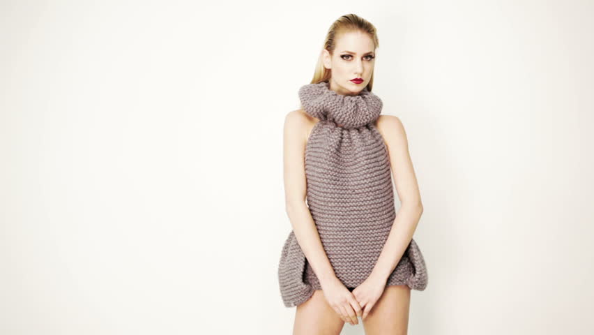 Fashion model strikes a pose and looks straight into the camera. Wears glamorous grey woollen dress. Expressive and stylish makeup and hairstyle.Dolly shot.