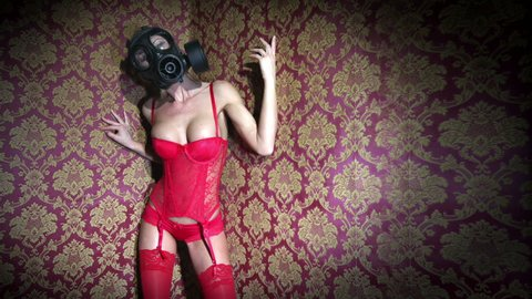 Burlesque or fetish style woman wearing gasmask and red lingerie