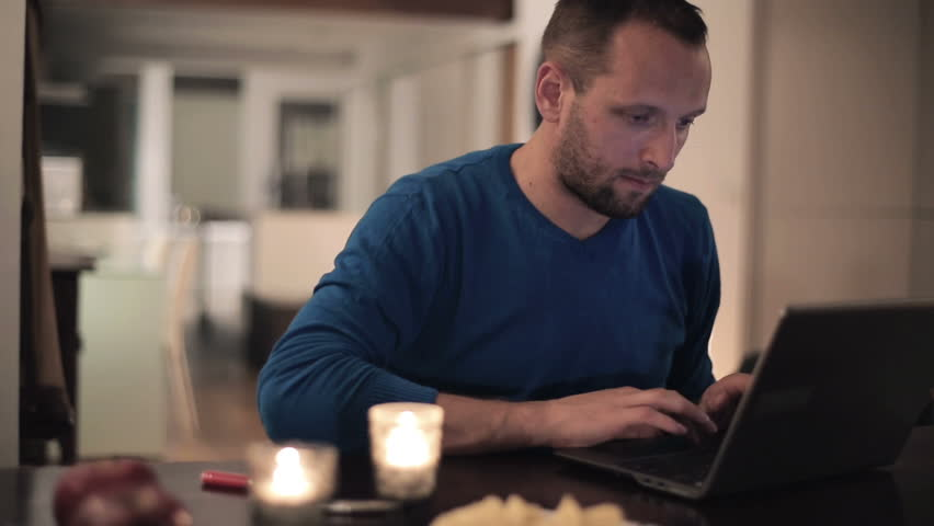 Young man with laptop sitting by the table at home