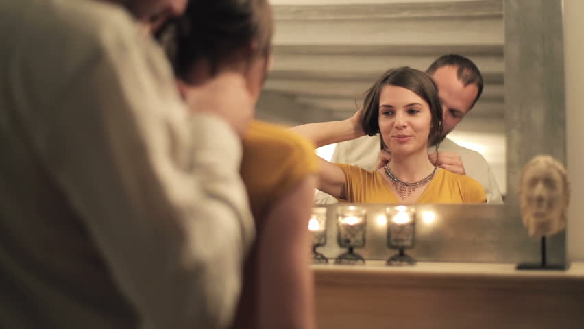 Man putting beautiful necklace on his wife neck in front of mirror