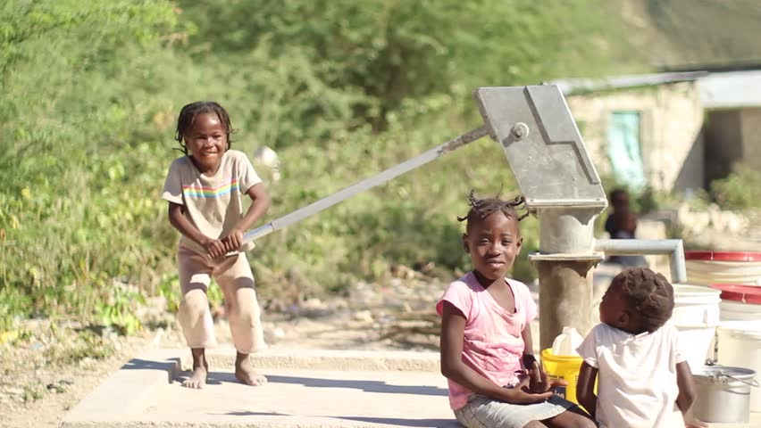 PORT AU PRINCE, HAITI - DECEMBER 17, 2013: Unidentified children pumping water at well in the outskirts of Port au Prince, Haiti.