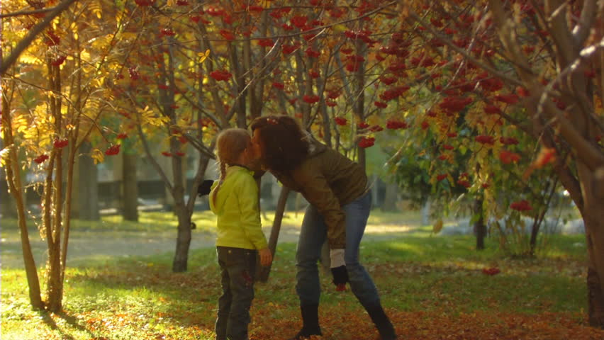Slow motion shot of the happy mum and little girl in autumn park