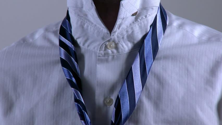 Closeup of a businessman tying a necktie.