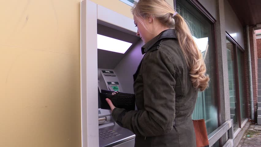 Woman withdrawing money at ATM, steadicam