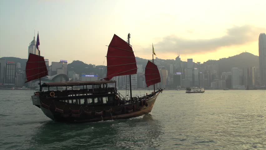 Junk ship in front of Hong Kong skyline during sunset
