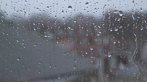 Heavy rain falling against large window pane, raindrops trickle down, grey sky with London houses outside