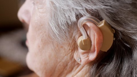 Elderly woman listening with hearing aid