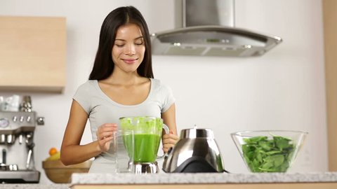 Woman making, pouring, drinking green vegetable smoothie with blender. Healthy eating lifestyle with young woman preparing blending smooithies drink with spinach, carrots, celery at home in kitchen.