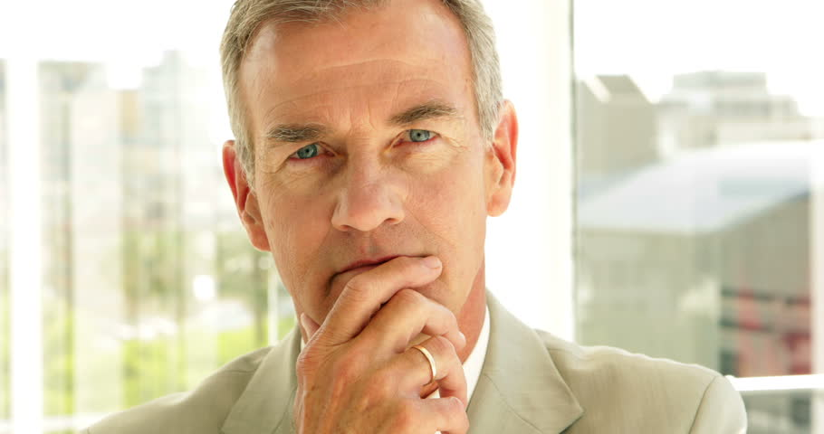 Thinking businessman looking at camera in his office