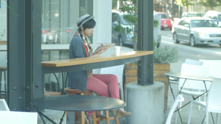 Urban Scene: Street Traffic And A Woman Seated At A Cafe With A Digital Tablet