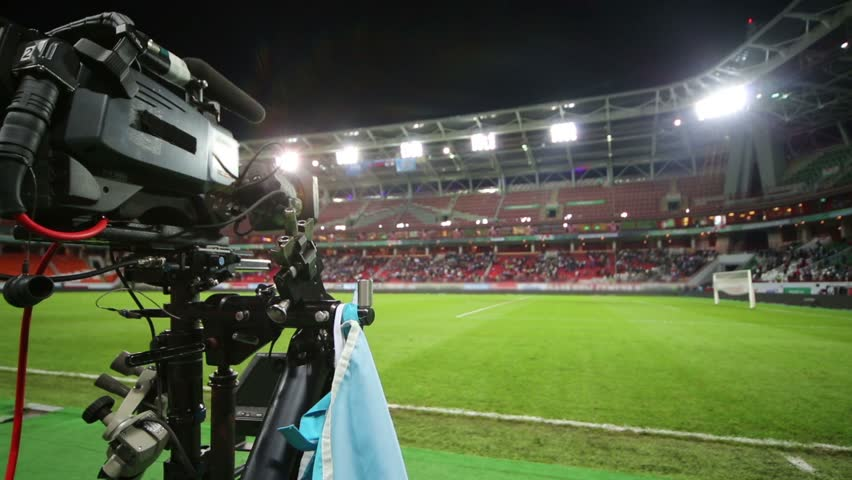 Video camera and empty green soccer field after match at stadium