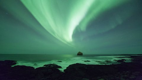 Aurora borealis seen off the rugged coast of Reykjanes, Iceland