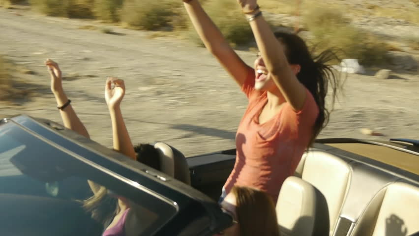 Girls Enjoy A Ride In A Convertible With Their Arms Raised