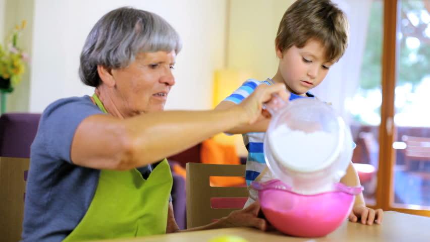 Senior woman having fun with grandson cooking