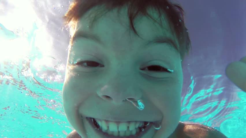 Cute teen boy dives in blue pool with open eyes | Shutterstock HD Video #5743244