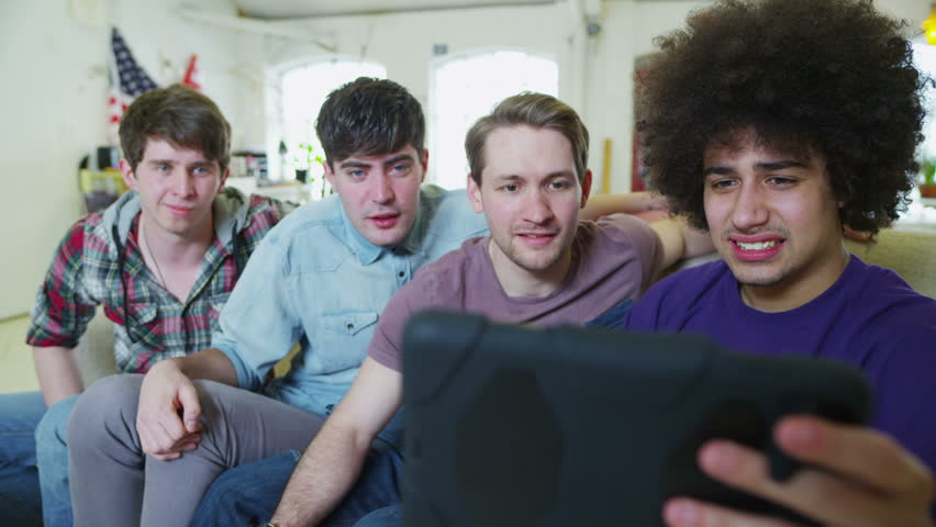Casual young male friends reacting to what they see on the screen of a computer tablet.