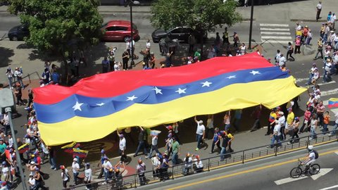 CARACAS, Venezuela Protest for freedom in Venezuela.  large crowd carries a flag.