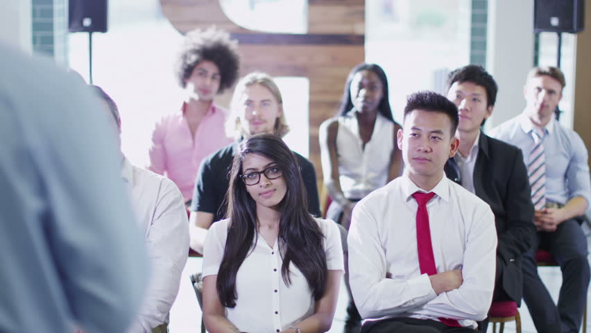 Cheerful diverse business group listening to the speaker at a business presentation or training seminar.    Shutterstock HD Video #5853290