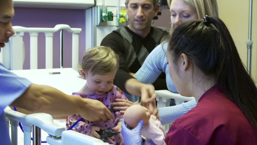 Toddler plays with nurse as pediatric team examine her.