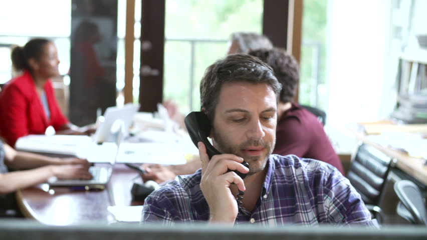 Camera tracks across office to show male architect on the phone working at desk whilst colleagues have meeting in background - he then has discussion with female colleague. | Shutterstock HD Video #5873066
