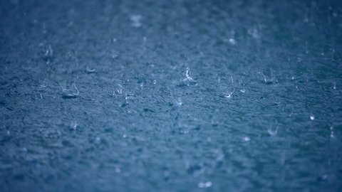 Raining water blue background, drops to puddle surface, wet weather, abstract liquid nature closeup video. Raindrop falling season. Splash, ripple on the road in rainy city, dark heavy storm outdoors.