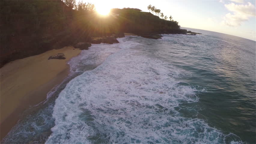 Gliding Aerial Drone Captures Waves Breaking Alongside Beautiful Pristine Beach During Sunset in Kauai Hawaii HD 1080 Video Slow Motion with Sun Flare Low Flying Forward Pan