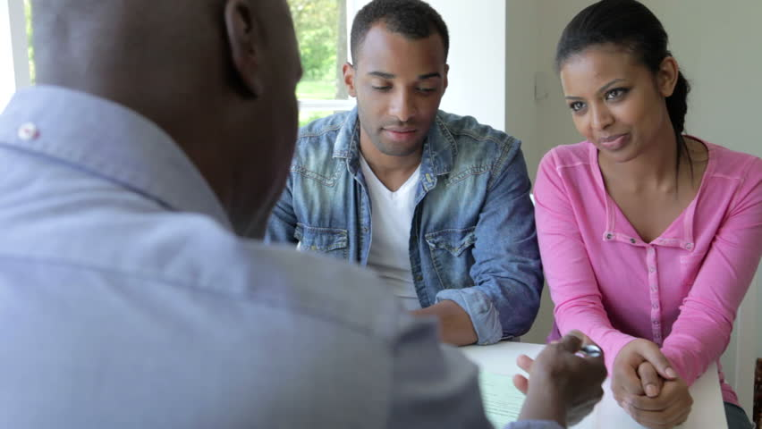 Young black couple discussing document with financial advisor before signing and shaking hands.Shot on Canon 5d Mk2 with a frame rate of 25fps