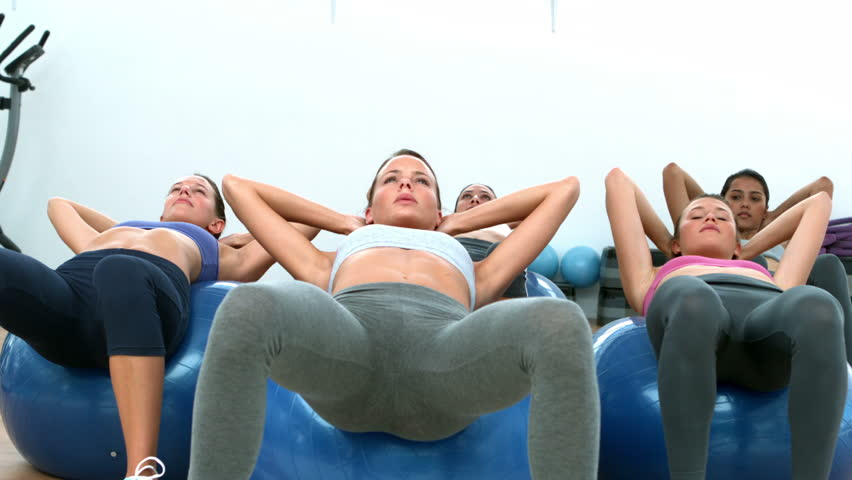 Fitness class doing sit ups on exercise balls in slow motion