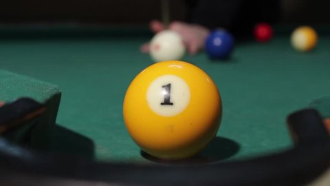 American billiard, 9-ball, nine-ball pool. Man playing billiard, snooker. Player preparing to shoot, hitting the cue ball and she hit yellow ball. Ball No.1 into the hole.Ball goes through the hole.