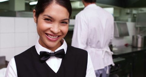 Smiling waitress being handed a dish by chef in a commercial kitchen