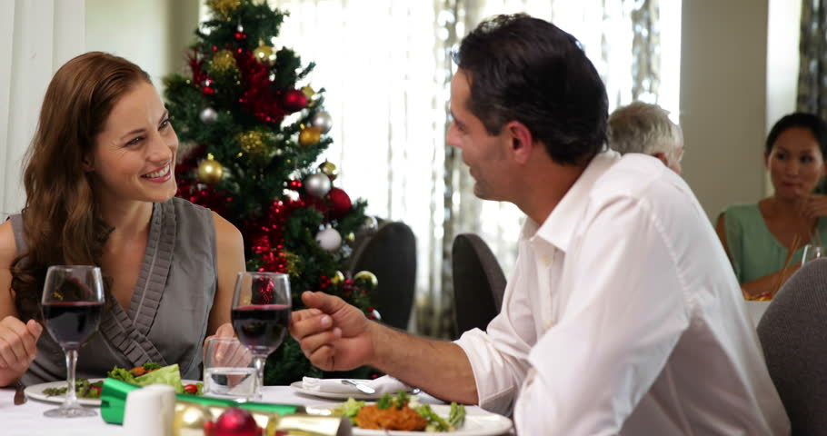 Happy Couple Having A Christmas Meal Together At Restaurant