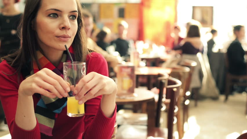 Young beautiful woman drinking juice in crowded cafe