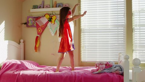 Young girl dressed as superheroes playing at home - 4K
