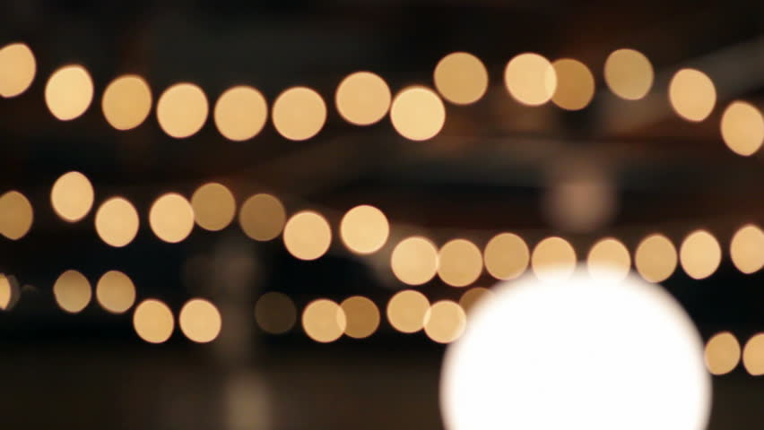Stringed lights out of focus, hanging outdoors