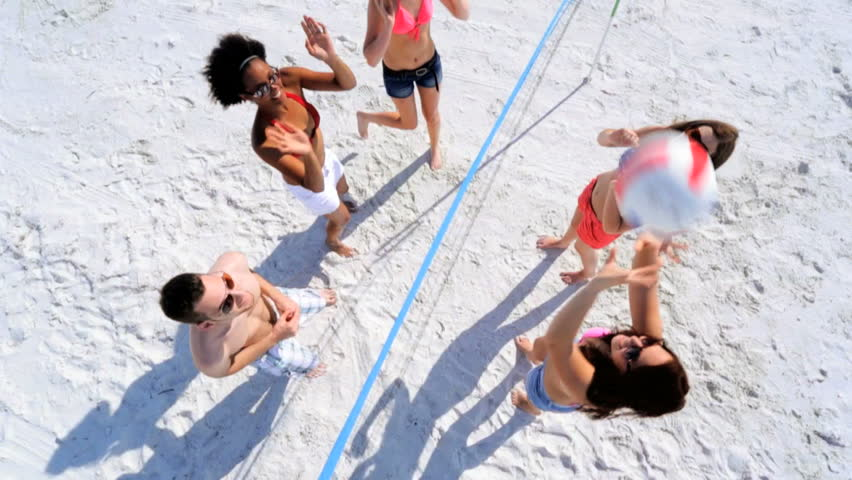 Group carefree boy girl teenagers casual beachwear enjoying beach volleyball on vacation together overhead view - Overhead Carefree Young People Vacation Beach Volleyball