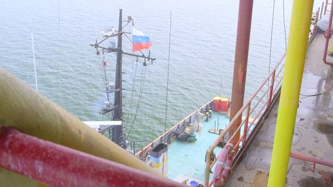 Offshore gas production platform in the East-Kazantip field, ship moored with Russian flag