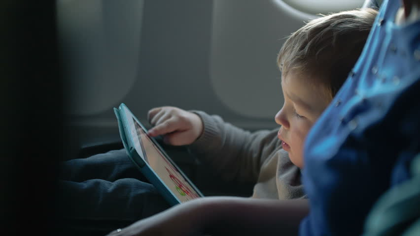Little boy traveling in an airplane sitting in his seat playing with a tablet computer watched by a parent | Shutterstock HD Video #6005240