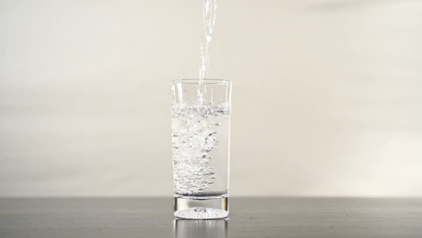 Pouring glass of water in slow motion until it overflows, and waters runs down the side and spills everywhere. You cannot fill your glass when it's already full.